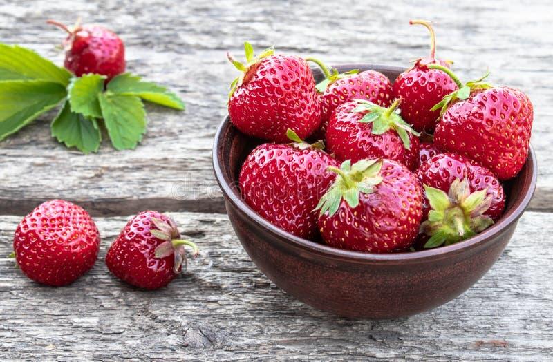 Nya jordgubbar i en bunke p? en tr?tabell arkivbild