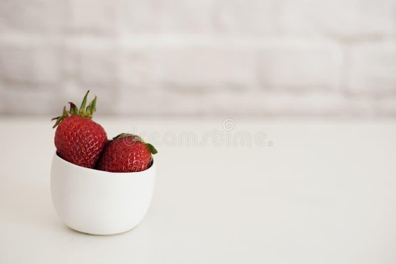 Nya jordgubbar i en liten vit bunke Vit bakgrund, tegelstenvägg ljus sammansättning royaltyfria foton