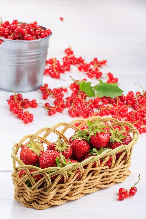 Nya jordgubbar i en vide- korg på en vit tabell arkivbild