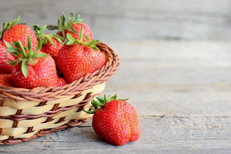 nya jordgubbar Mogna saftiga jordgubbar i en vide- korg och på tappningen trätabell Naturlig källa av vitaminer arkivbilder