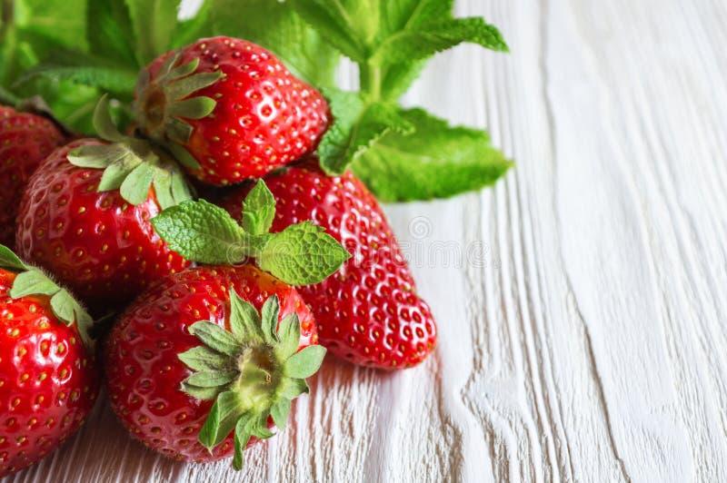 Nya jordgubbar och mintkaramellsidor på vit träbakgrund royaltyfri fotografi
