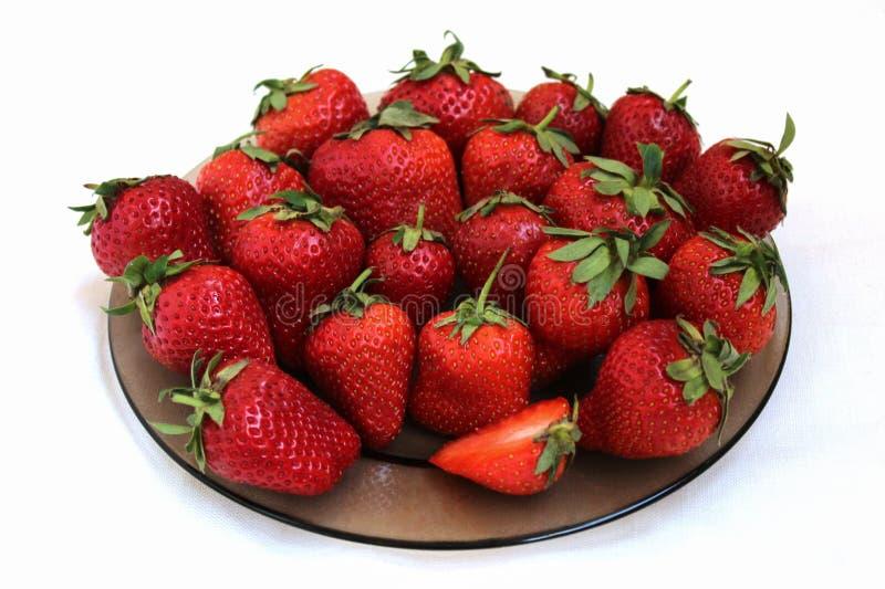 Nya jordgubbar på en platta, närbild, på en vit bakgrund royaltyfria foton