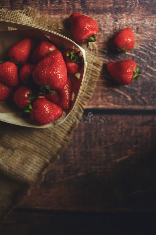 Nya jordgubbar på en trätabell, ecoplatta arkivfoton