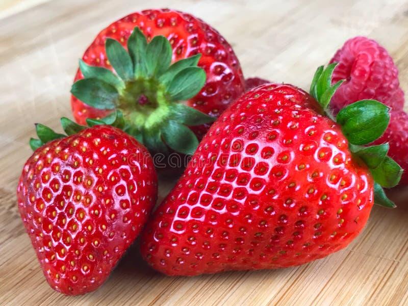 Nya jordgubbar på träskärbräda royaltyfri foto