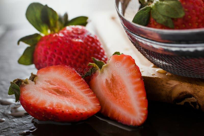 Nya jordgubbar som är saftiga på trätabellen på ett kök royaltyfri bild