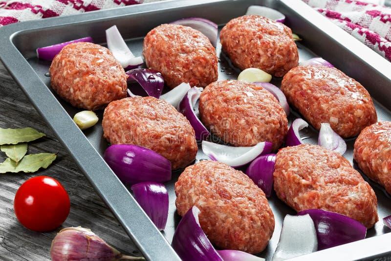 Nya jordkotletter för rått kött i bakningmaträtt arkivbild