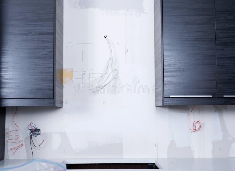 Nya köksskåp, elektriskt ledningsnät, uttag, kopplar installation royaltyfria bilder