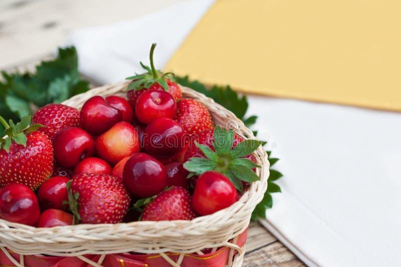 Nya körsbär och röda mogna jordgubbar på en vit platta arkivfoton