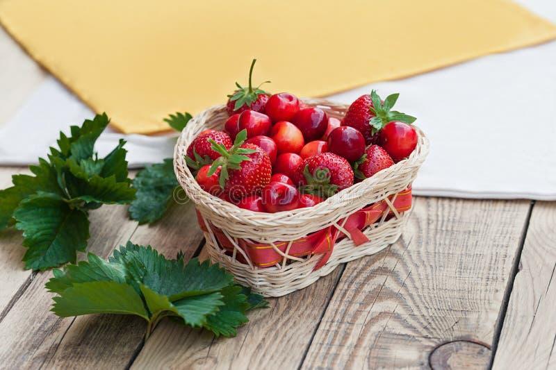 Nya körsbär och röda mogna jordgubbar på en vit platta arkivbild