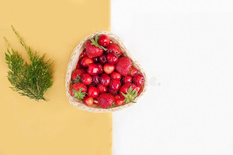 Nya körsbär och röda mogna jordgubbar på en vit platta royaltyfri bild