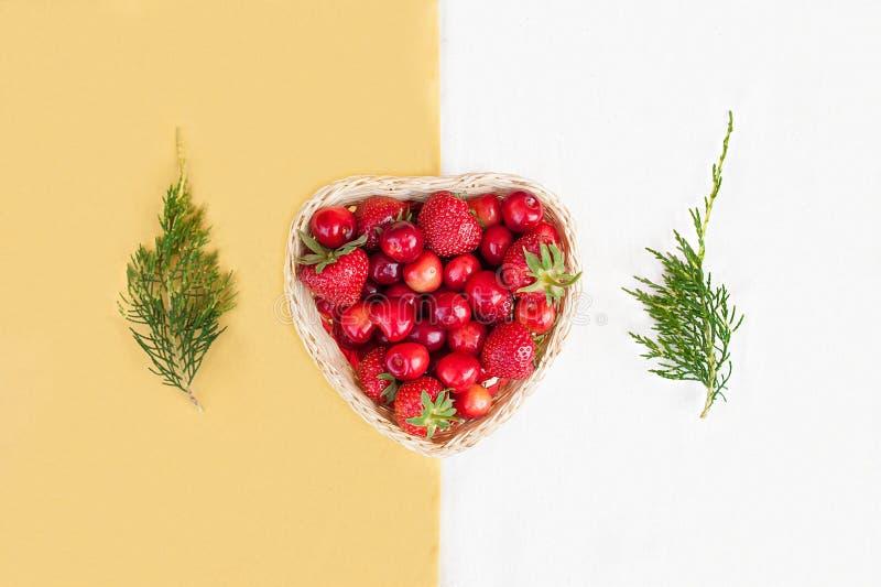 Nya körsbär och röda mogna jordgubbar på en vit platta royaltyfria bilder