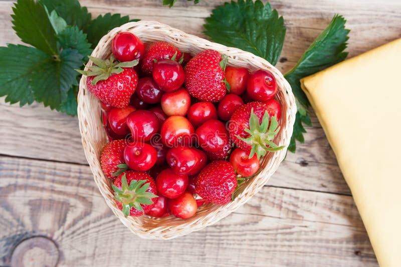 Nya körsbär och röda mogna jordgubbar på en vit platta arkivfoto