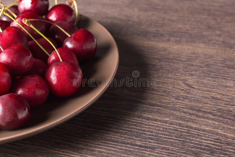 Nya körsbär på en brun platta på en trätabell Sommarmat, sunt äta Organiskt vegetariskt, strikt vegetarian, diet- som är diabetis arkivfoton