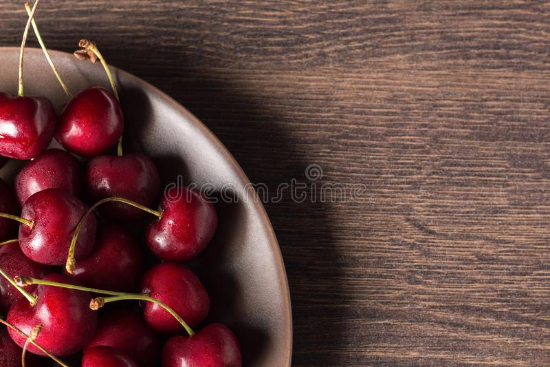 Nya körsbär på en brun platta på en trätabell Sommarmat, sunt äta Organiskt vegetariskt, strikt vegetarian, diet- som är diabetis fotografering för bildbyråer