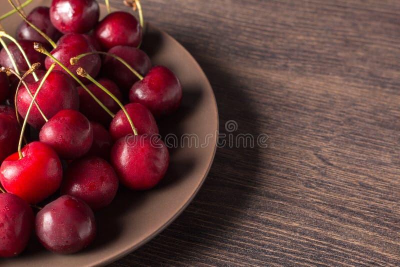 Nya körsbär på en brun platta på en trätabell Sommarmat, sunt äta Organiskt vegetariskt, strikt vegetarian, diet- som är diabetis royaltyfri fotografi