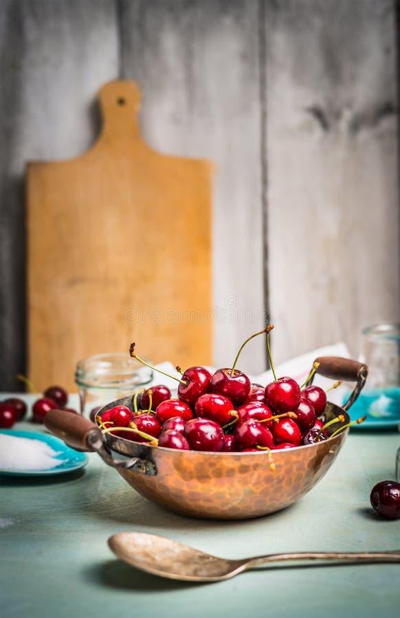 Nya körsbärbär i gammal panna på lantlig kökbakgrund arkivfoton