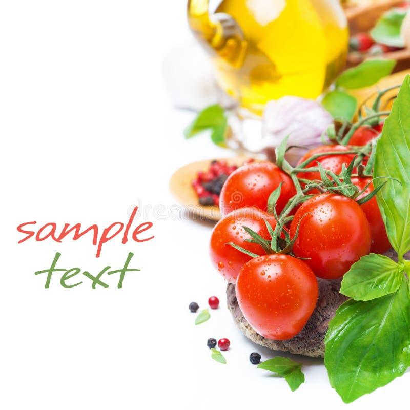 Nya körsbärsröda tomater, basilika och kryddor som isoleras fotografering för bildbyråer