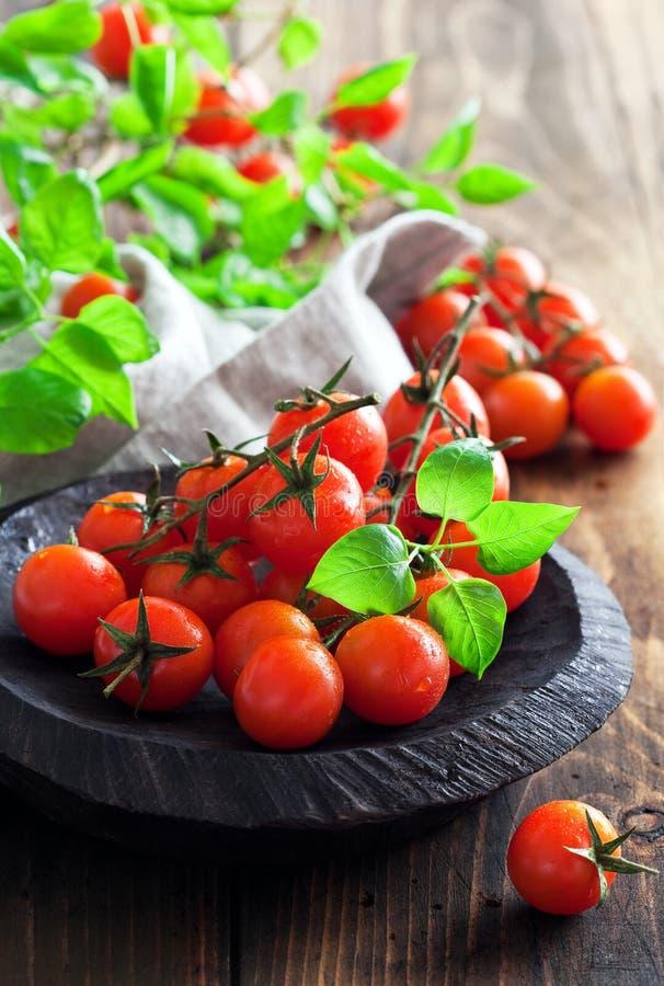 Nya körsbärsröda tomater i en träbunke arkivbild