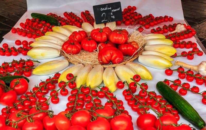 Nya körsbärsröda tomater, tomater på vinrankan och endiv som är till salu på lokala utomhus- bönder, marknadsför i Nice, Frankrik royaltyfria bilder