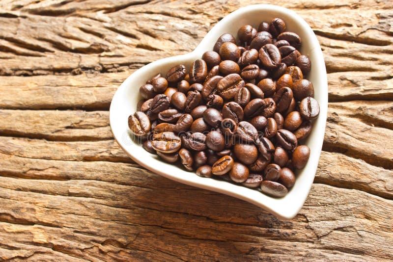 Nya kaffebönor i den vita hjärtakoppen arkivbilder