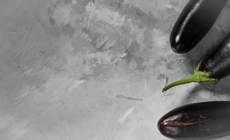 Nya kokta aubergine ligger på en grå kökyttersida arkivbilder