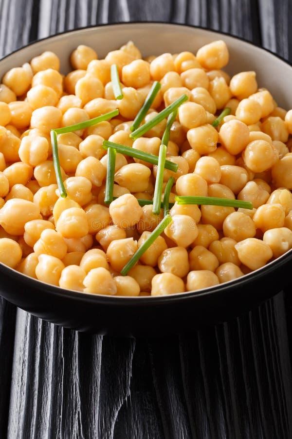 Nya kokta organiska kikärtar med salladslöknärbild i en bunke vertikalt royaltyfria foton