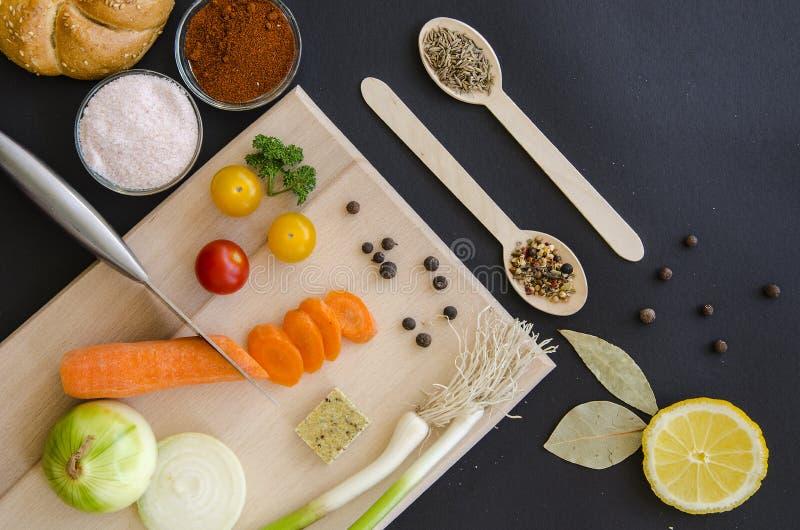Nya läckra ingredienser för sund matlagning- eller salladdanande på bakgrund för mörk svart och träskärbräda royaltyfria bilder