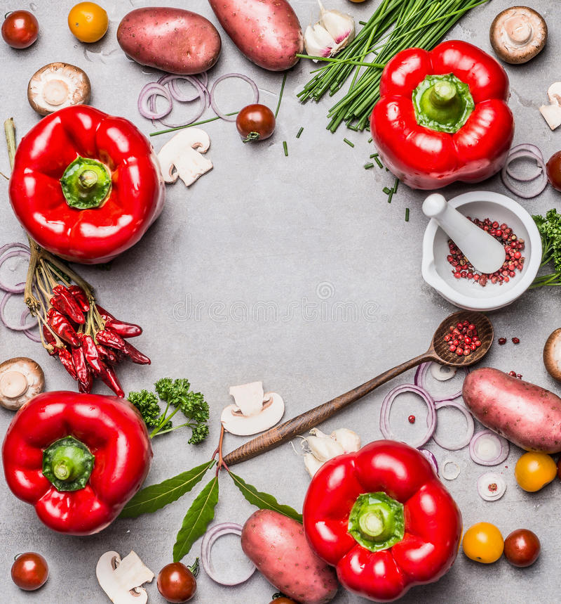 Nya läckra säsongsbetonade grönsaker och ingredienser med röd paprika, örter, träskeden och kryddamortel på grå färger hårdnar te royaltyfria bilder