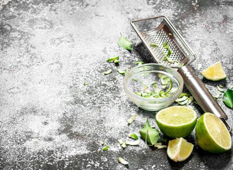 Nya limefrukter med rivjärnet och piff i en bunke fotografering för bildbyråer
