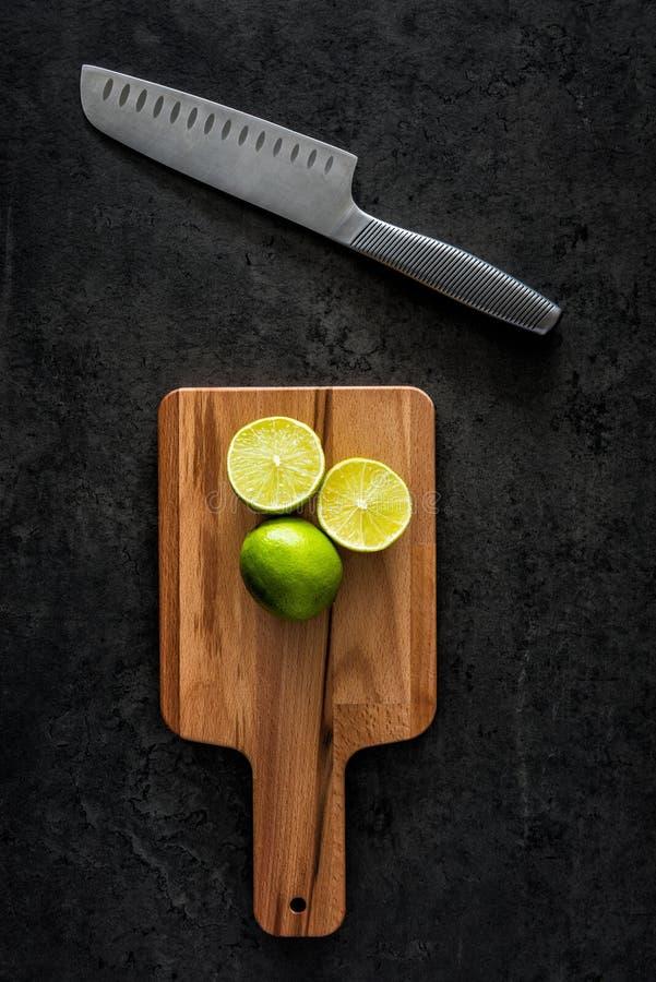 Nya limefrukter på skärbräda med kniven på den svarta stentabellen royaltyfria bilder