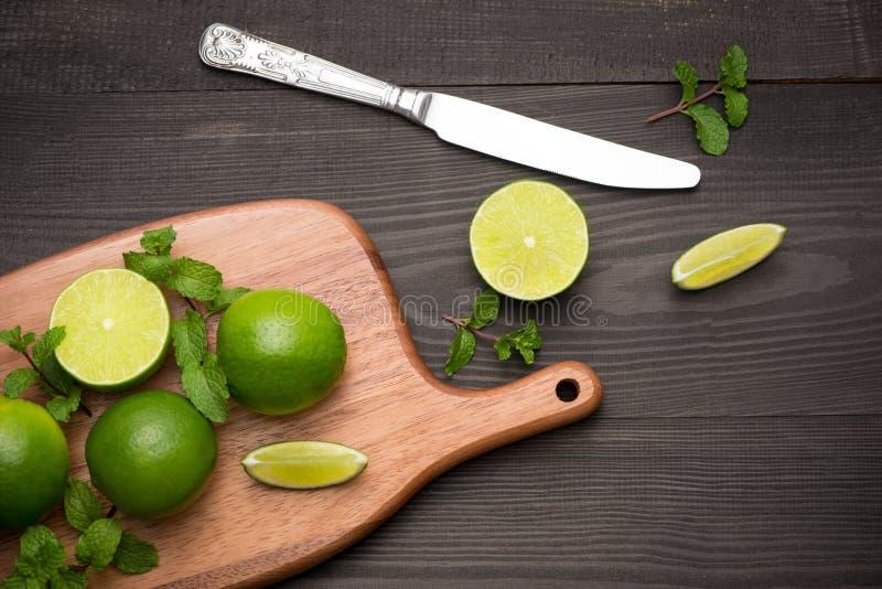 Nya limefrukter på skärbräda på trätabellen Bästa sikt, backgrou arkivfoton