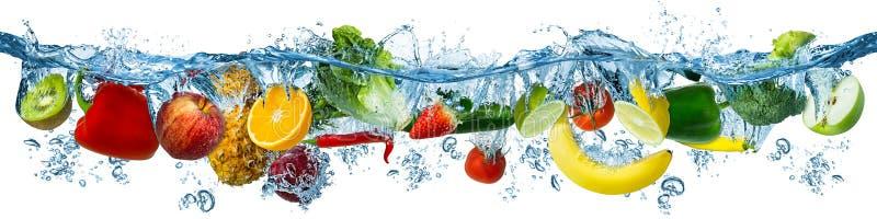 Nya mång- frukter och grönsaker som plaskar in i blå klar vattenfärgstänk som, sund mat bantar friskhetbegrepp, isolerade vitt arkivfoto