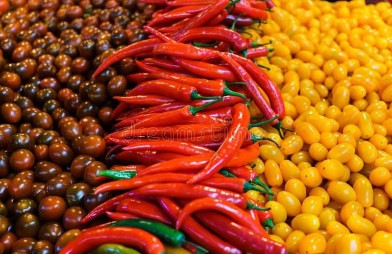 Nya mångfärgade körsbärsröda tomater och glödheta peppar arkivfoto