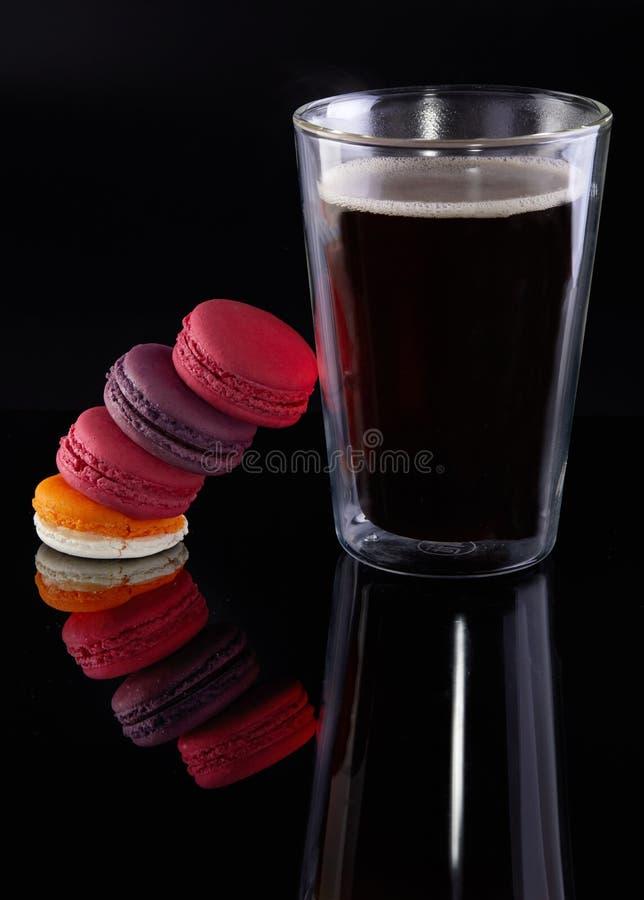 Nya macarons av olika färger och anstrykningar och ett exponeringsglas av espressokaffe på en svart bakgrund arkivfoto