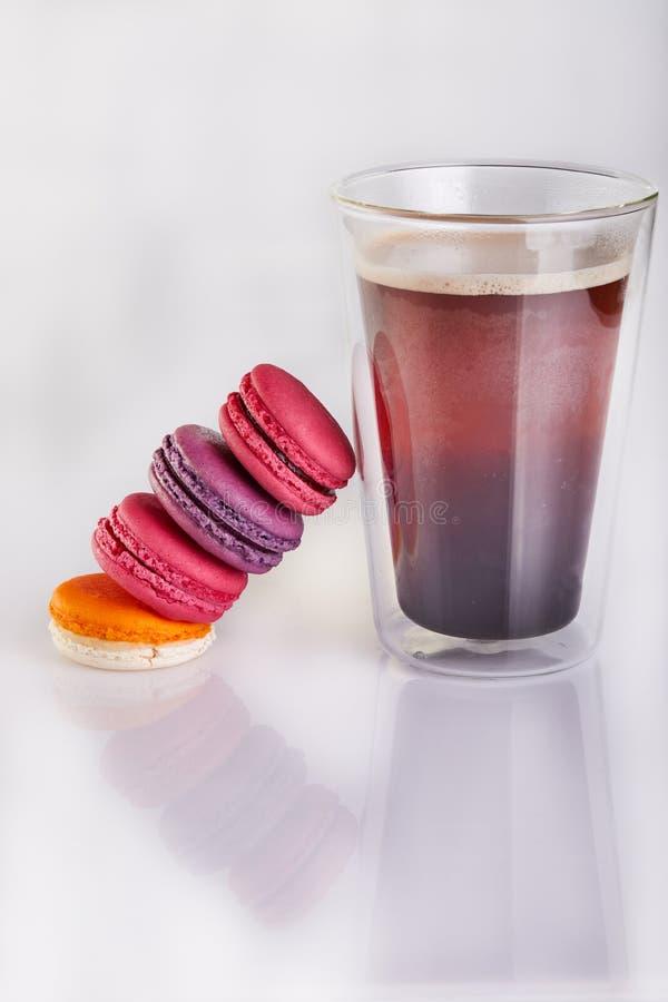 Nya macarons av olika färger och anstrykningar och ett exponeringsglas av espressokaffe på en vit bakgrund royaltyfria foton