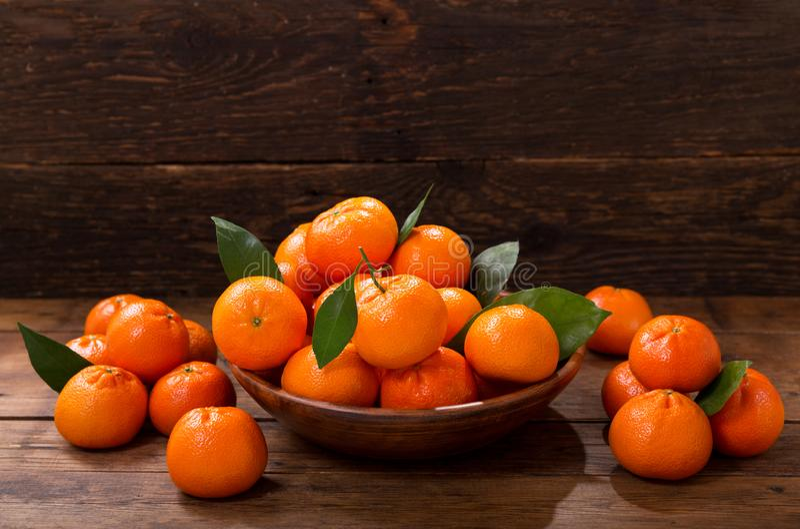 Nya mandariner bär frukt eller tangerin med sidor i en bunke royaltyfri fotografi