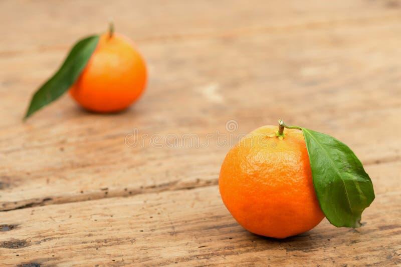 Nya mandariner bär frukt med sidor i gammal trätabell royaltyfria bilder