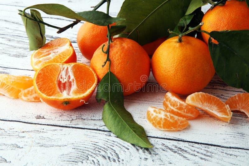 Nya mandariner bär frukt med sidor på trätabellen royaltyfria bilder