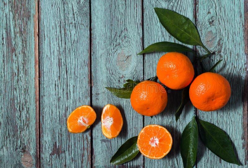 Nya mandariner frukt eller tangerin med sidor i en platta på turkosträtabellen royaltyfri fotografi