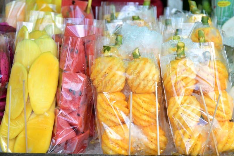 Nya mango-, melon- och ananasfrukter som skivas i plastpåsar I arkivbilder
