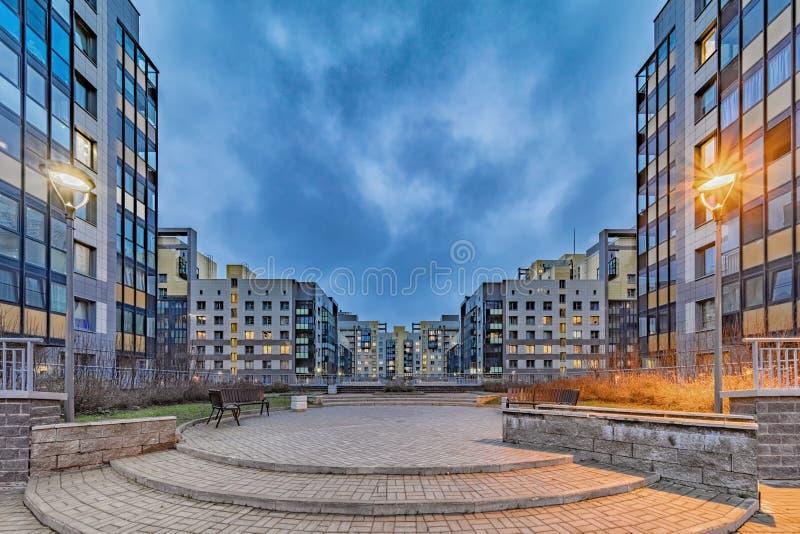 Nya moderna bostadshus med belysta fönster royaltyfri fotografi