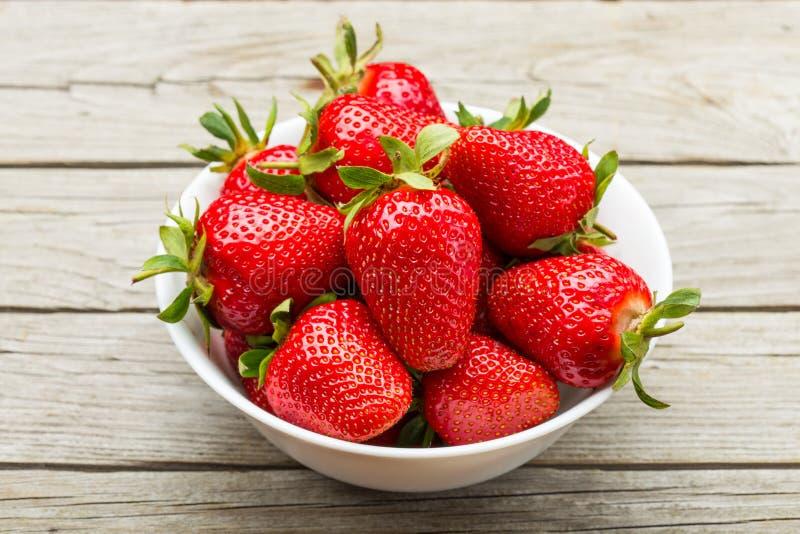 Nya mogna jordgubbar i en enkel vit bunke royaltyfri fotografi