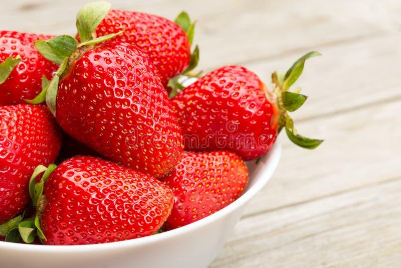 Nya mogna jordgubbar i en enkel vit bunke fotografering för bildbyråer