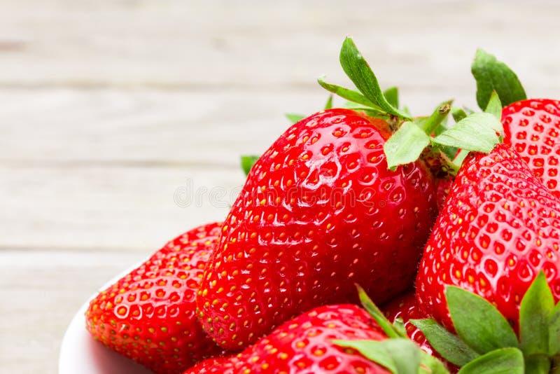 Nya mogna jordgubbar i en enkel vit bunke royaltyfria foton