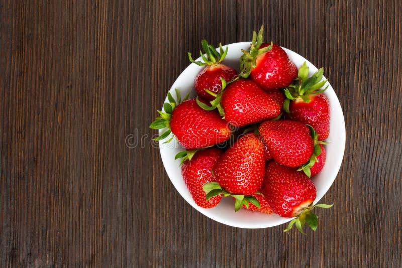 Nya mogna jordgubbar i en enkel vit bunke royaltyfri bild