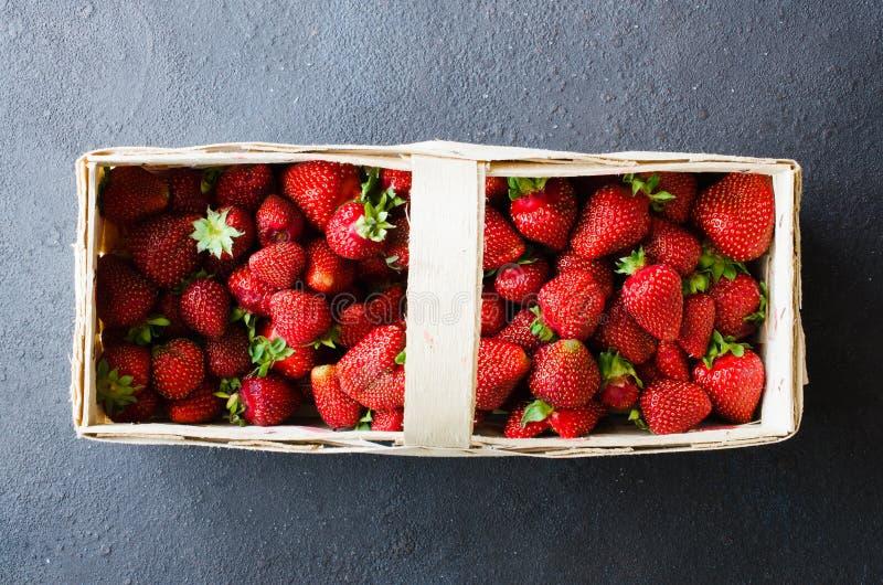 Nya mogna jordgubbar i en träkorg på en mörk bakgrund Organiska saftiga bär fotografering för bildbyråer