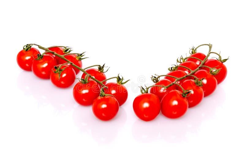 Nya mogna körsbärsröda tomater på vit bakgrund royaltyfria bilder