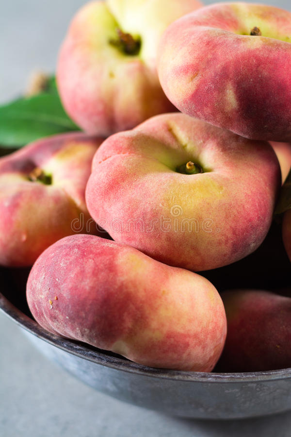Nya mogna kineslägenhetsaturn persikor med sidor arkivbilder