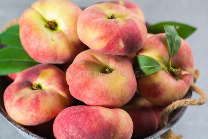 Nya mogna kineslägenhetsaturn persikor med sidor arkivfoto
