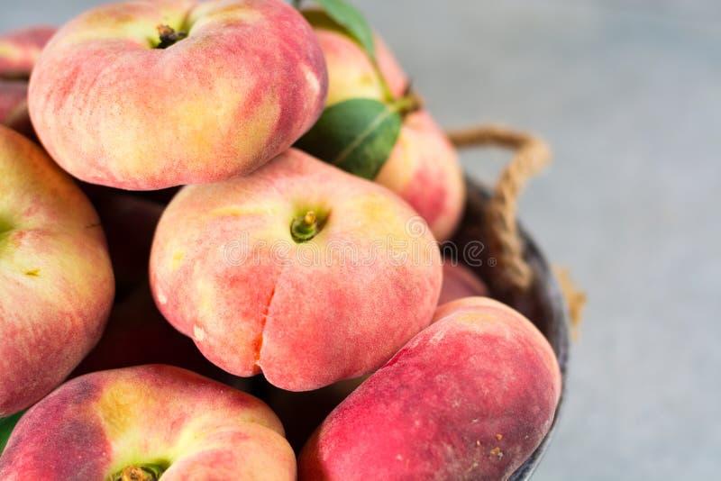 Nya mogna kineslägenhetsaturn persikor med sidor royaltyfria foton